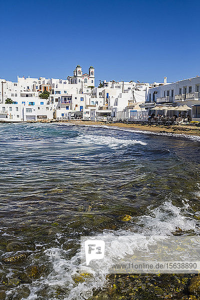 Waterfront of Naoussa with beach  restaurant patio and traditional white buildings; Naoussa  Paros Island  Cyclades  Greece