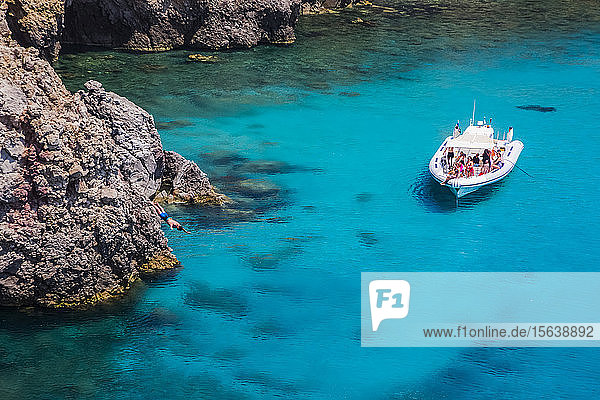 Tourists on a tour boat at Tsigado Beach  with a young man diving off a cliff; Milos Island  Cyclades  Greece