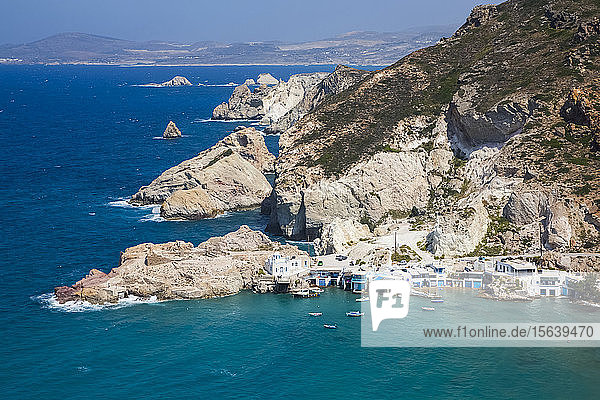 Fyropotamos Village with boats in the small harbour and a view of the rugged coastline; Fyropatamos  Milos Island  Cyclades  Greece
