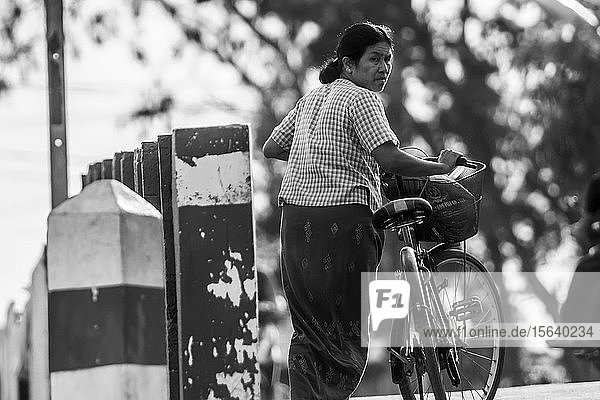 Black and white image of a Burmese woman with a bicycle; Yawngshwe  Shan State  Myanmar
