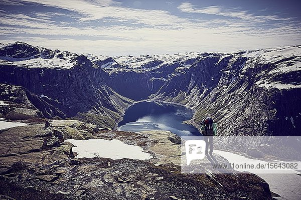 Junge Frau beim Bergsteigen zum Trolltunga  Ausblick in den Fjord  Sørfjord  bei Odda  Norwegen  Europa