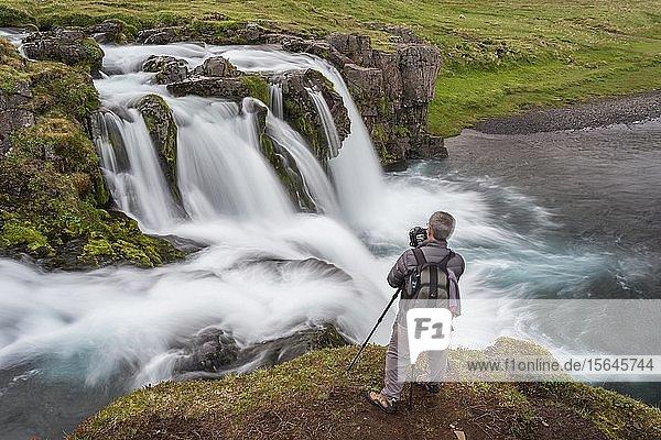 Fotograf vor Wasserfall in Landschaft von Westisland  Vesturland  Island  Europa