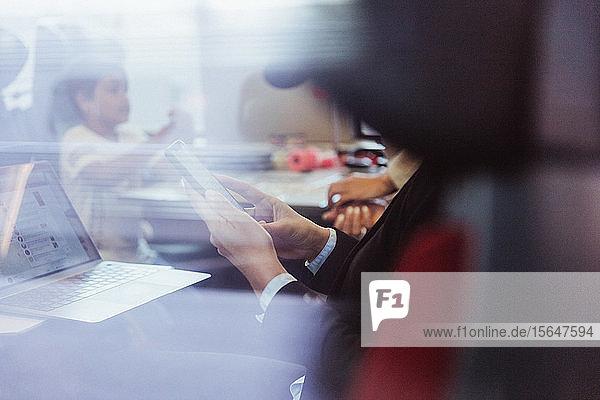Mittelsektion einer Geschäftsfrau mit Laptop  die ein Smartphone benutzt  während sie im Zug sitzt