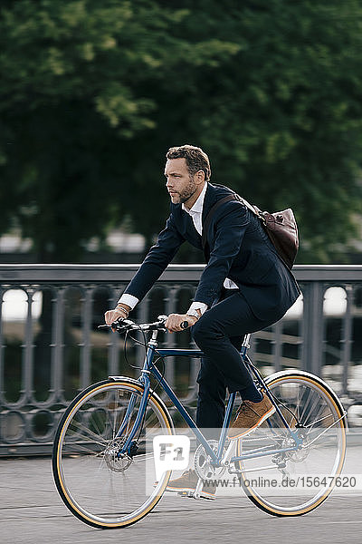 Full length of confident businessman riding bicycle on road in city