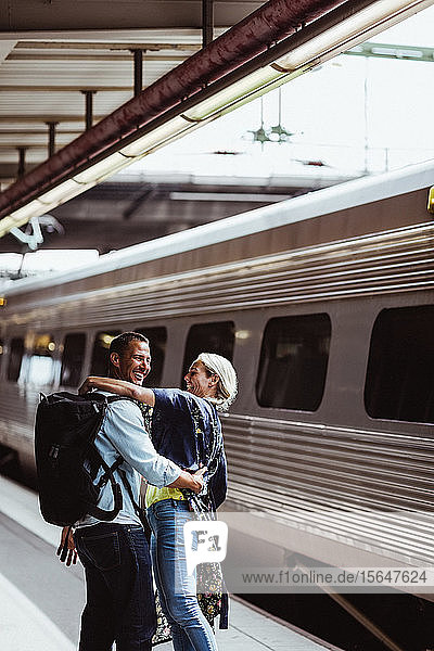 Happy couple embracing by train at railroad station