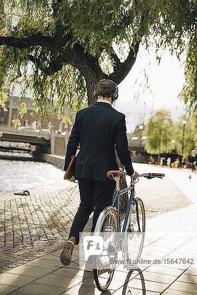 Rückansicht eines Geschäftsmannes zu Fuß mit dem Fahrrad auf einem Fußweg in der Stadt