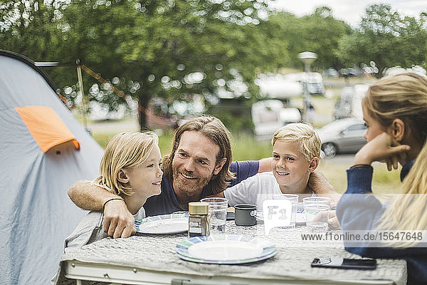 Smiling father sitting with children at table in camping site
