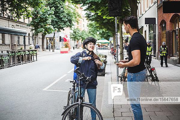 Lieferfrau im Gespräch mit einem männlichen Kunden  der in der Stadt auf dem Bürgersteig steht