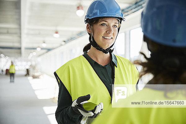 Zuversichtliche Ingenieurin im Gespräch mit Kollegen auf der Baustelle