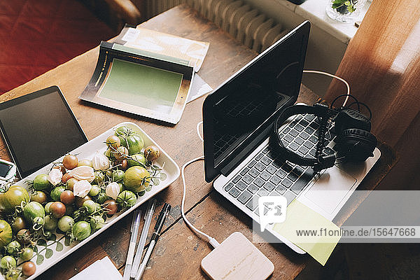 High angle view of laptop with headphones by tomatoes in tray on table at home