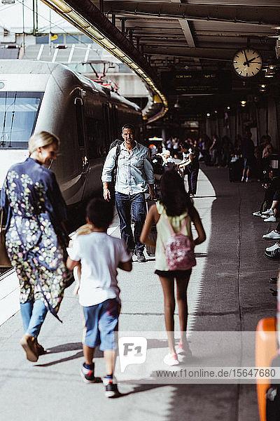 Familie zu Fuss mit dem Zug auf dem Bahnsteig des Bahnhofs