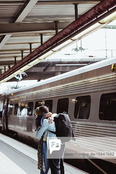 Mann und Frau umarmen sich bei der Begrüßung im Zug auf dem Bahnsteig des Bahnhofs