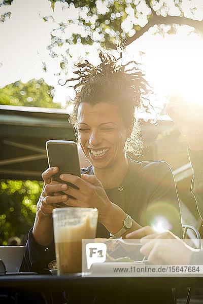 Lächelnde Architektin beim Mobiltelefonieren während eines Mittagessens mit einer Mitarbeiterin im Außencafé an einem sonnigen Tag