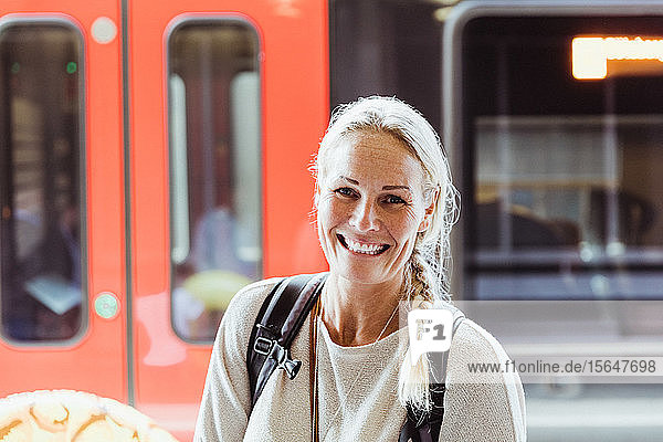 Portrait of smiling mature woman with backpack standing at train station