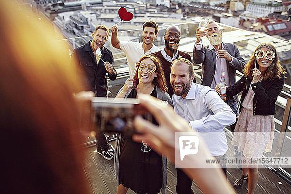 Glückliche Kollegen posieren beim professionellen Fotografieren auf Büroparty