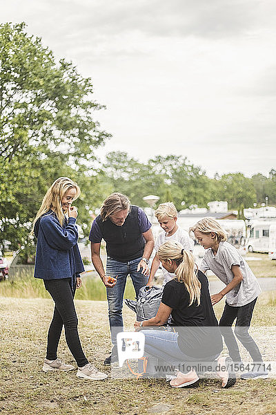 Family looking at woman unpacking tent at camping site