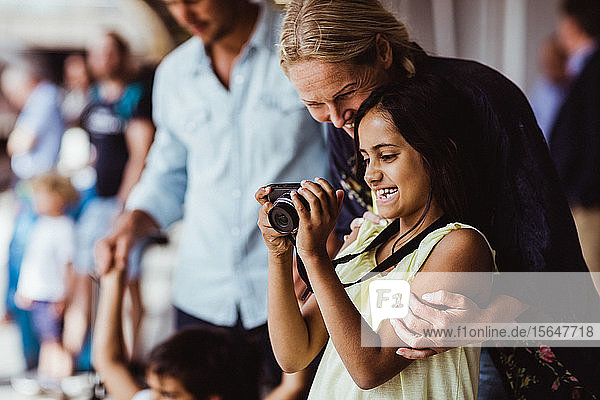Happy daughter showing camera to mother while standing by family at station