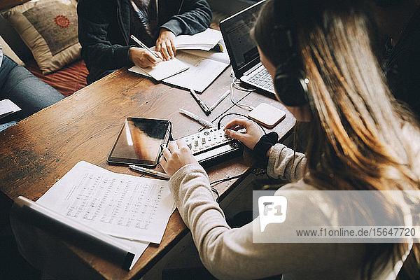 Hochwinkelansicht eines Teenager-Mädchens  das eine Audioanlage benutzt  während es Hausaufgaben am Tisch im Zimmer macht