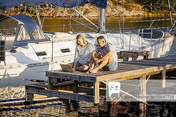 Ehepaar diskutiert über Laptop  während es an einem sonnigen Tag mit einer Yacht am Pier sitzt