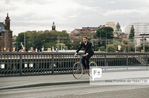 Geschäftsmann fährt Fahrrad auf Straße in Stadt gegen Himmel