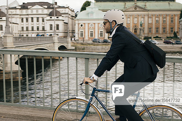 Side view of businessman riding bicycle on bridge by canal in city