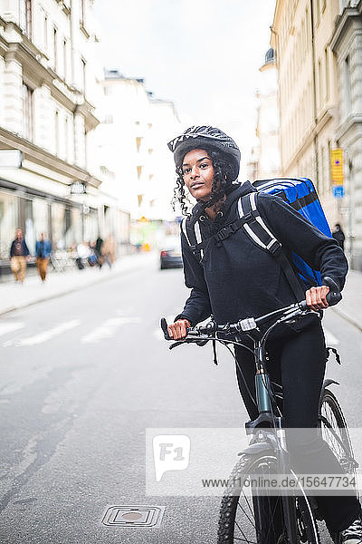 Delivery woman looking away while standing with bicycle on street in city