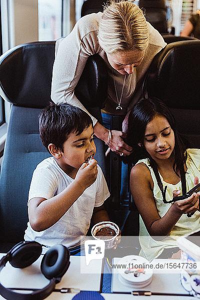 Mädchen zeigt Mutter und Bruder eine Kamera  während sie im Zug unterwegs sind