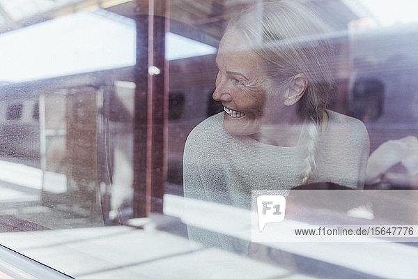 Lächelnde reife Frau schaut durch Fenster  während sie im Zug reist