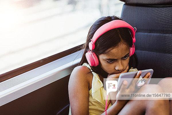 Mädchen mit rosa Kopfhörern schaut sich einen Film auf ihrem Handy an  während sie im Zug am Fenster sitzt