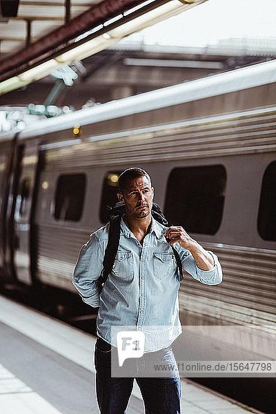 Männlicher Tourist mit Rucksack im Zug  der am Bahnhof wegschaut