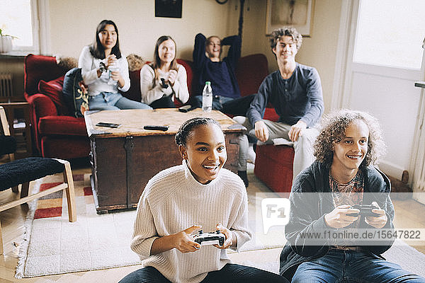 Happy teenagers playing video game while friends sitting on sofa in living room