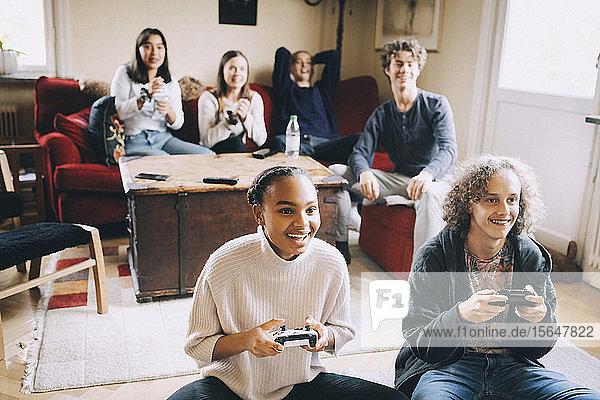 Glückliche Teenager spielen Videospiele  während Freunde auf dem Sofa im Wohnzimmer sitzen