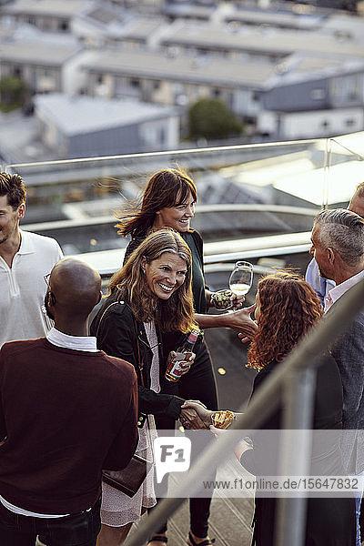 Fröhliche Begrüßung von Fachleuten bei einer Party auf der Terrasse nach Feierabend