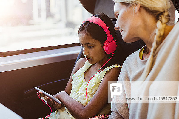 Mutter schaut Tochter an  die während einer Zugfahrt auf einem Smartphone einen Film ansieht