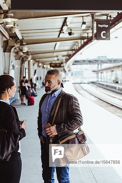 Coworkers talking while standing at railroad station platform during business travel
