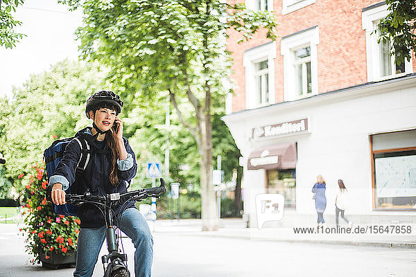 Food delivery woman talking on smart phone at street in city