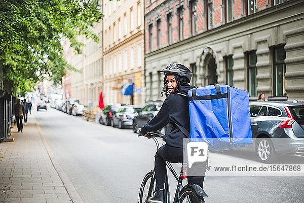 Porträt einer lächelnden Lieferfrau mit Fahrrad auf der Straße in der Stadt