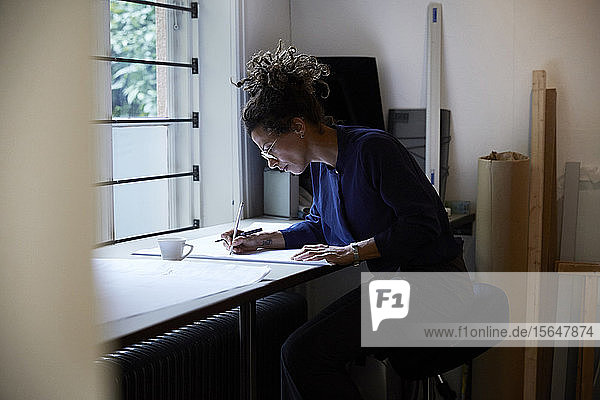Side view of confident female architect working in office