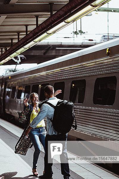 Fröhliches Paar umarmt sich im Zug auf dem Bahnsteig