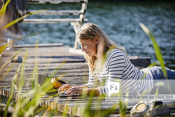 Woman lying on front while working over laptop at pier during summer