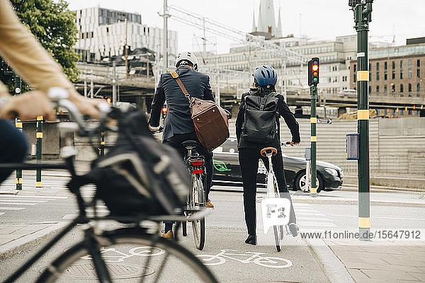 Rückansicht eines Geschäftsmannes und einer Geschäftsfrau mit Fahrrädern auf der Straße in der Stadt