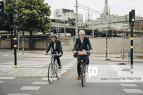 Smiling businessman and businesswoman riding bicycles on road in city