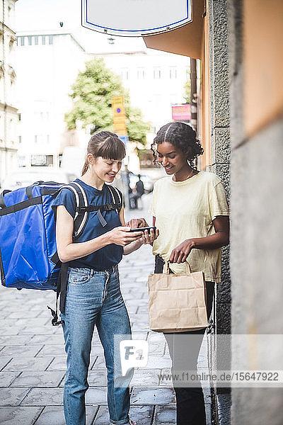 Lächelnde Zustellfrau nimmt beim Zustellen des Pakets das Zeichen des weiblichen Kunden entgegen