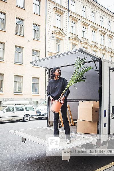 Möbelpackerin entlädt Topfpflanze vom Lastwagen auf der Straße in der Stadt