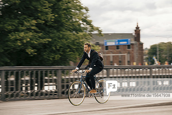 Full length of confident businessman riding bicycle on city street