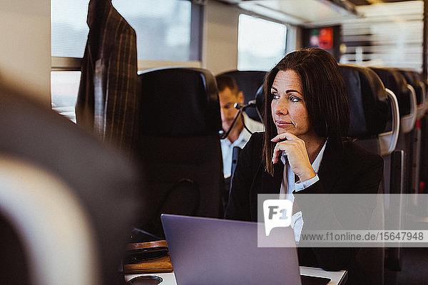 Nachdenklicher Geschäftspendler benutzt Laptop  während er im Zug wegschaut