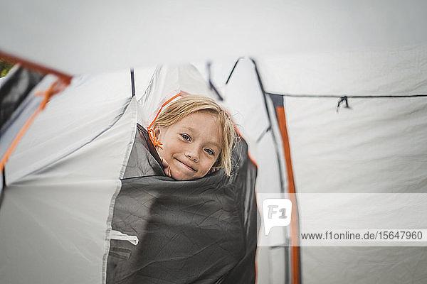 Portrait of smiling girl peeking through tent at campsite