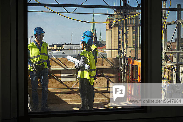 Male and female engineers seen through window at construction site
