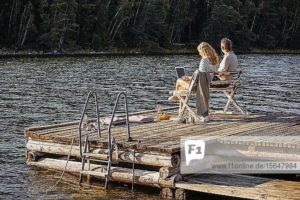 Mann und Frau mit Laptop  während sie im Sommer auf einer Bank über dem Pier am See sitzen