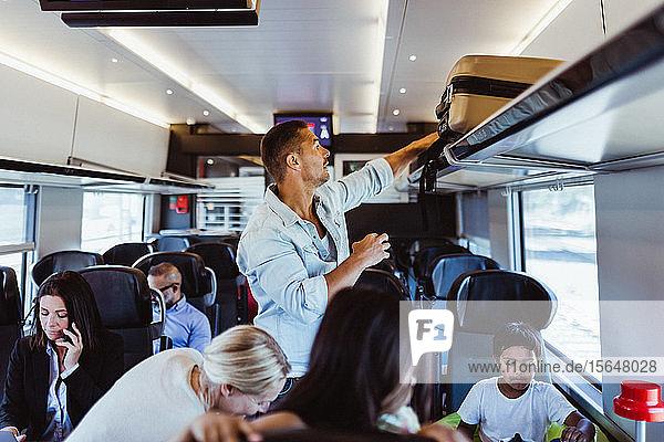 Mann richtet Koffer im Regal aus  während er mit der Familie im Zug während der Ferien reist